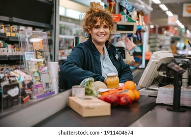 Portrait of a woman sitting behind checkout counter smiling at camera. Supermarket cashier at checkout.