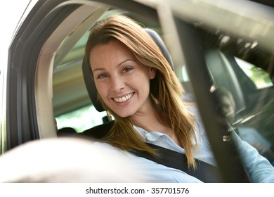 Portrait of woman sitting in car with family
