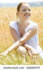portrait of woman sitting in grain field