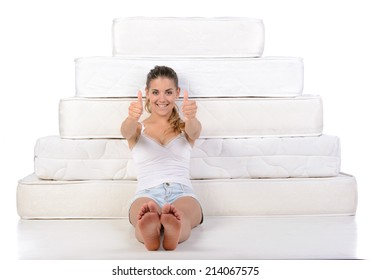 Portrait of a woman sitting near many mattresses. Orthopedic mattress.