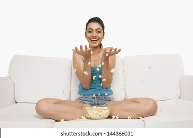 Portrait of a woman sitting on a couch and spreading popcorn