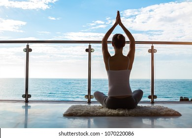 Portrait of a woman sitting on the mat on the seaside view balcony with hands up in yoga pose - rear view.