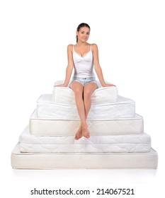 Portrait of a woman sitting on a lot of mattresses. Orthopedic mattress.