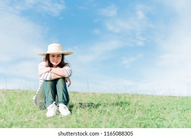 Portrait of a woman sitting on the mountain with a bright sky in the spring.
