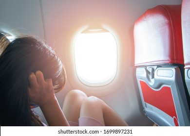 Portrait of a woman sitting on a plane by the window is stressed worry uneasy dismal unhappy upset expression sunlight and flare background concept Travel.