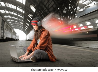 Portrait of a woman sitting on a platform and working on a laptop