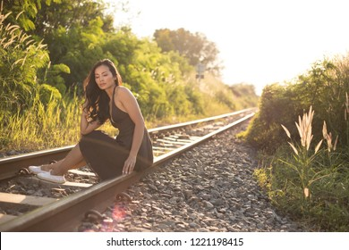 Portrait of woman sitting on a railway in the rays of sunset.