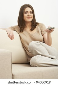 Portrait of woman sitting on sofa and holding remote control panel TV