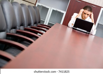 Portrait of woman sitting at the table with laptop on it and thinking about new business-plan
