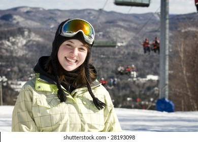 Portrait of woman skier with chairlift and mountains behind