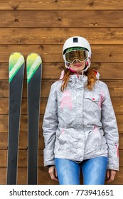 portrait woman skier with skis and helmet near wooden wall.