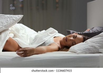 Portrait of a woman sleeping deeply on a bed at home in the night