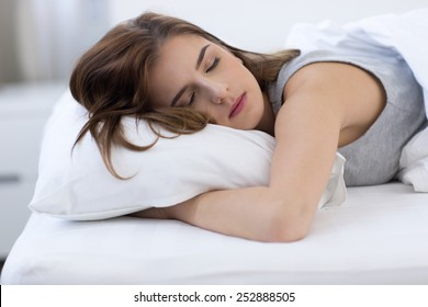 Portrait of a woman sleeping on the bed at home