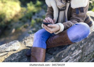 Portrait of a woman with a smartphone outdoors