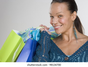 Portrait of woman smiling with gift bags over shoulder