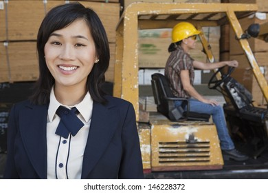 Portrait of woman smiling while female industrial worker driving forklift truck in background