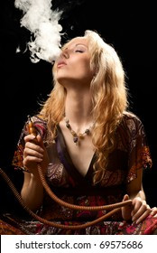 Portrait of a woman smoking hookah. Black background. Studio shot.