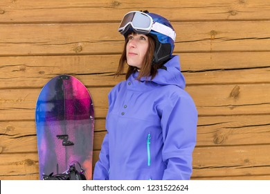 portrait woman with snowboard and hat and splitboard near wooden wall