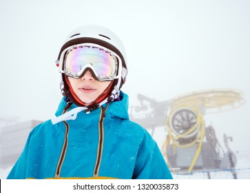 Portrait of woman snowboarder on background of falling snow and snow gun in the snowy weather in the high mountains of the Caucasus at Krasnaya Polyana