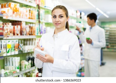 Portrait of woman specialist who is standing near shelves in drugstore