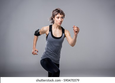 portrait of woman in sportive clothing running in earphones isolated on grey