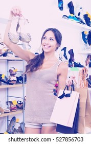 Portrait of woman standing in boutique with shopping bags and chosen shoes in boutique