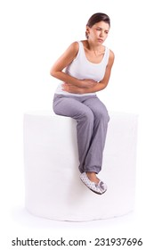 Portrait of woman with stomach ache sitting on a roll of toilet paper, her hands on abdomen