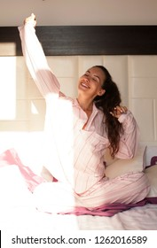 Portrait of woman stretching after sleep in bed