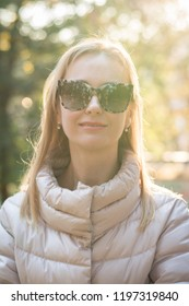 Portrait woman in sunglases in autumn park