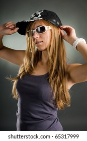 portrait of a woman with sunglasses and basecap in the studio