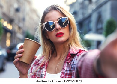 Portrait of woman in sunglasses taking photo on the smartphone.