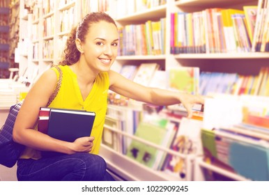 Portrait woman taking literature books in store with prints