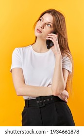 Portrait woman talking on mobile phone and looking away isolated over yellow background - Shutterstock ID 1934661878