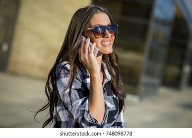 Portrait of woman talking over mobile phone outdoor