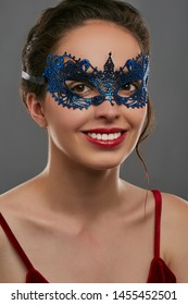 Portrait of woman with tied back brunette hair, wearing wine red crop top. The smiling girl is looking at the camera, wearing blue carnival mask with perforation. Vintage women's carnival accessory.