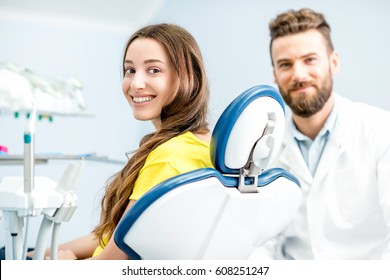 Portrait of a woman with toothy smile sitting at the dental chair with doctor on the background at the dental office