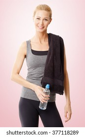 Portrait of a woman with a towel in her shoulder standing at isolated background and holding a bottle of water in her hand.