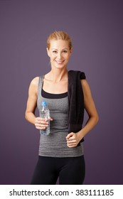 Portrait of a woman with a towel on her shoulder holding a water bottle and standing against at white background.