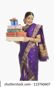 Portrait of a woman in traditional Assamese dress holding gifts and smiling