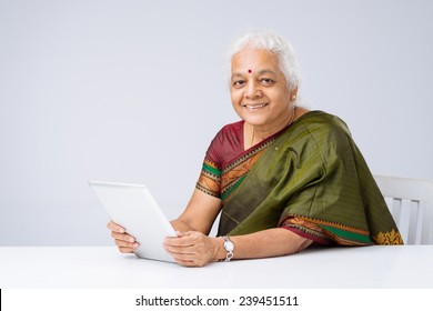 Portrait of woman in traditional Indian clothes sitting at table with a digital tablet