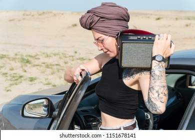 Portrait of a woman in a turban standing at a car with a bluetooth column on her shoulder, against the background of the desert