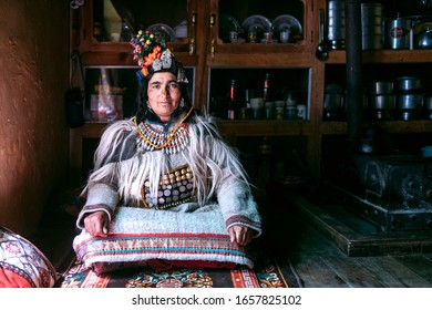 Portrait of a woman in typical tibetan clothes inside her house in Ladakh, Kashmir, India.