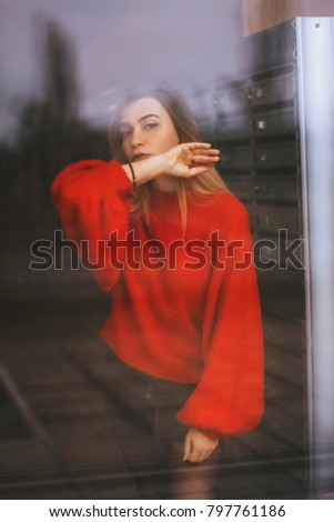 6df9704818 Woman in black skirt and red top near the window. postal cell on  background. Fashion look. - Image