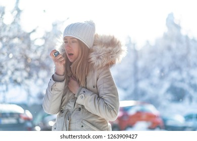 Portrait of a woman using an asthma inhaler in a cold winter. Woman with Inhaler Suffering Asthma Attack in Winter Asthmatic patient managing condition with medication in cold season