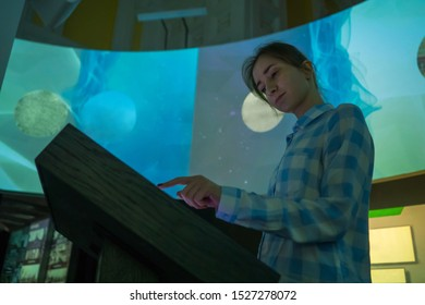 Portrait of woman using interactive touchscreen display of electronic multimedia kiosk at modern museum or exhibition. Evening time, low light illumination. Education, learning and technology concept