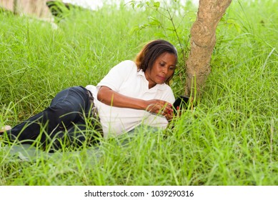 Portrait of woman using mobile phone on the grass. single person lying and relaxing in the park