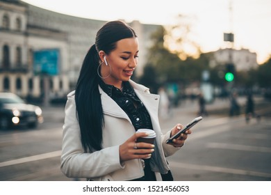 Portrait of woman using mobile phone while holding coffee cup on the city street