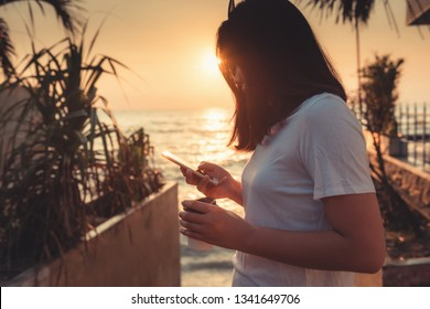 Portrait of Woman is Using Smartphone at The Beach Duration Summer Vacation, Asian Tourist is Relaxing With Her Cell Phone on The Beach in Holiday Time. Technology Communication Concept.