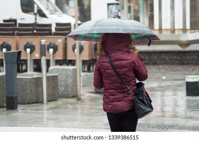 portrait of woman walking with  umbrella in the pedestrian street