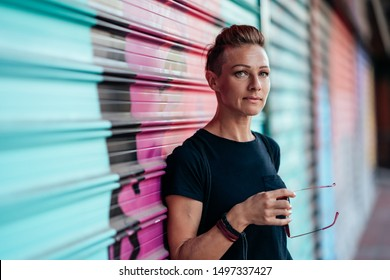 Portrait of woman wearing black shirt and mohawk hairstyle standing against garage door